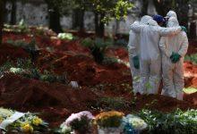 Foto de coveiros em frente a sepulturas